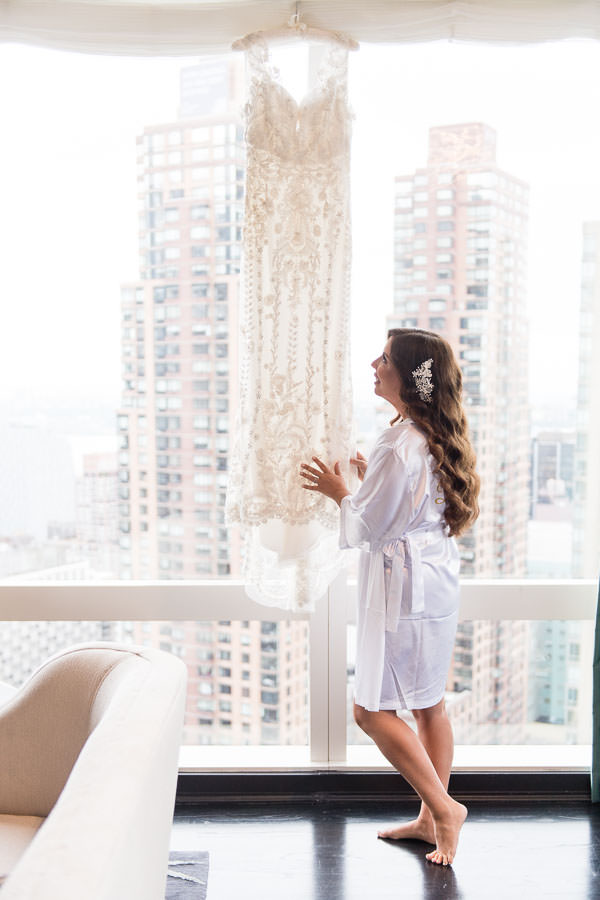 bride and dress hanging from the window at the mandarin oriental hotel in nyc