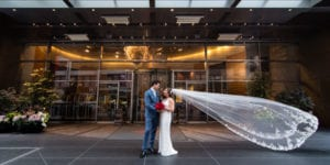 bride and groom outside entrance of mandarin oriental with veil flowing in the wind