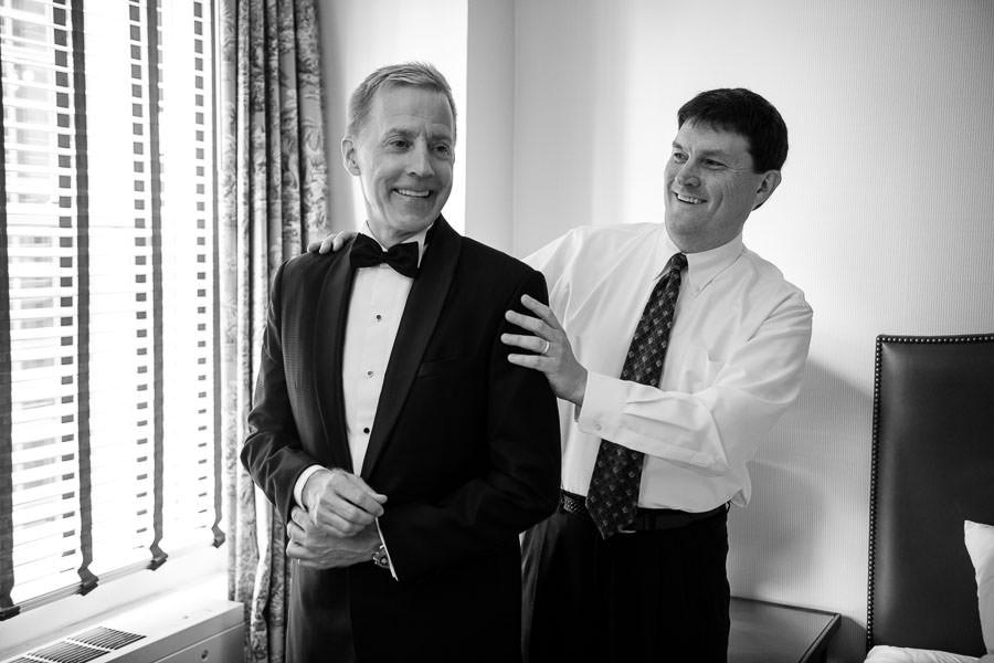groomsmen helps groom with his jacket during groom prep