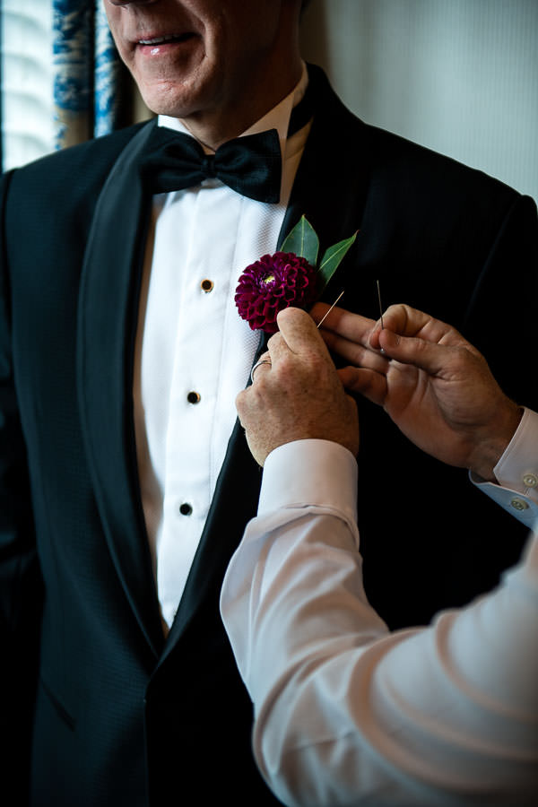 best man helps groom with boutonniere