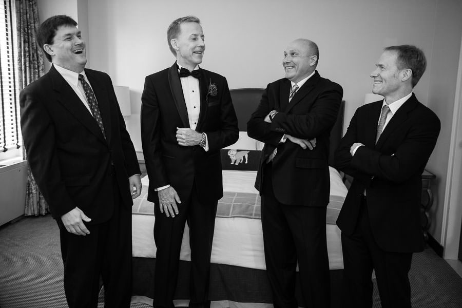 groom and groomsmen wait in the hotel room of yale club in new york city in a semicircle laughing