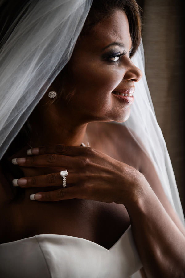 bride looks out the window and waits for her groom