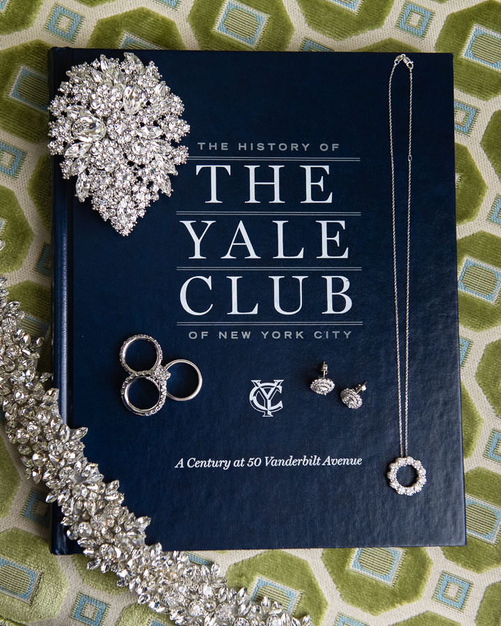 bride's jewelry for her wedding at the yale club on top of a yale club book