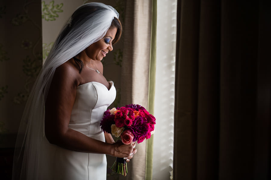 bride holds her flowers by window during bride prep