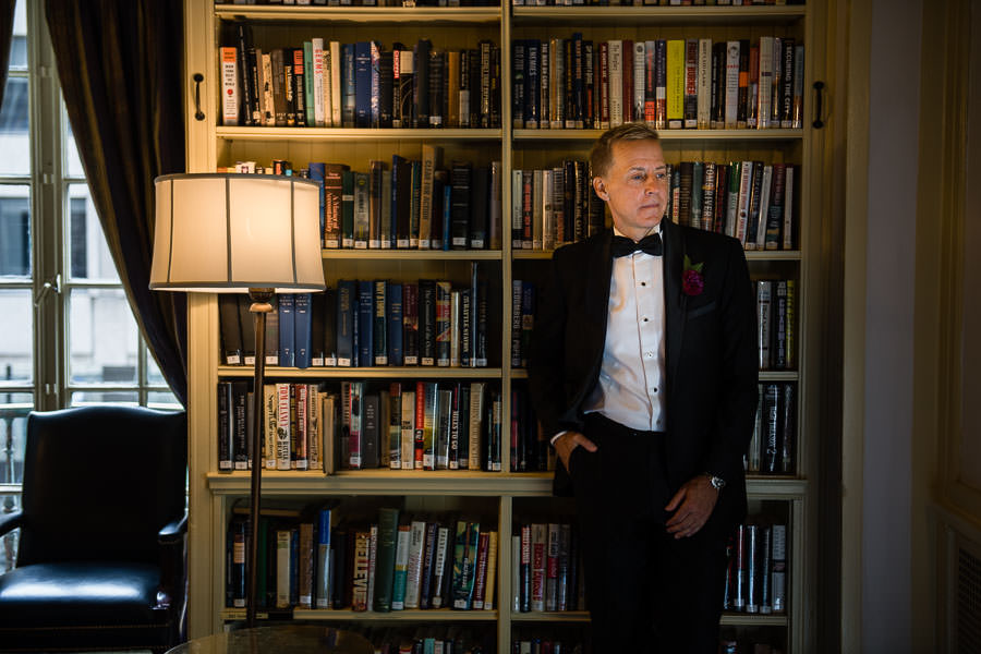 bruce waits for his bride leaning against a bookshelf during groom prep at yale club nyc