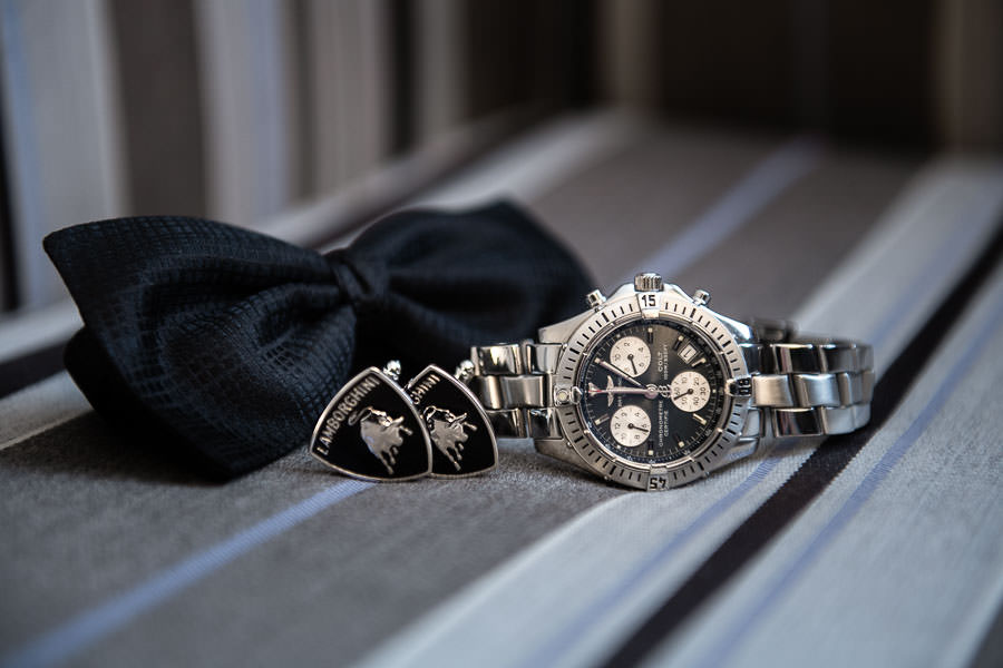 detail photo of breitling watch and cuff links and bow tie during wedding groom prep at yale club nyc