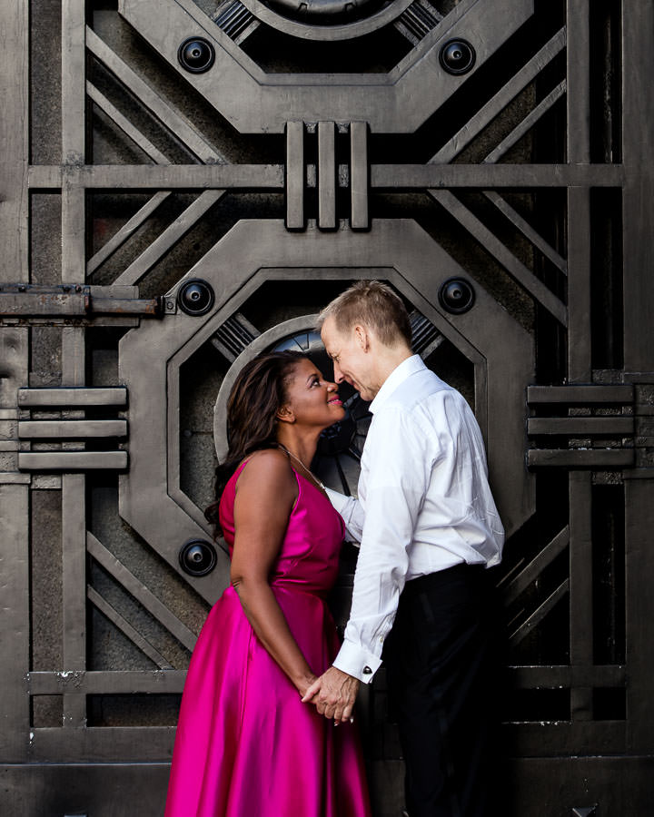 engaged couple in formal evening wear in front of large door for their engagement session in downtown manhattan