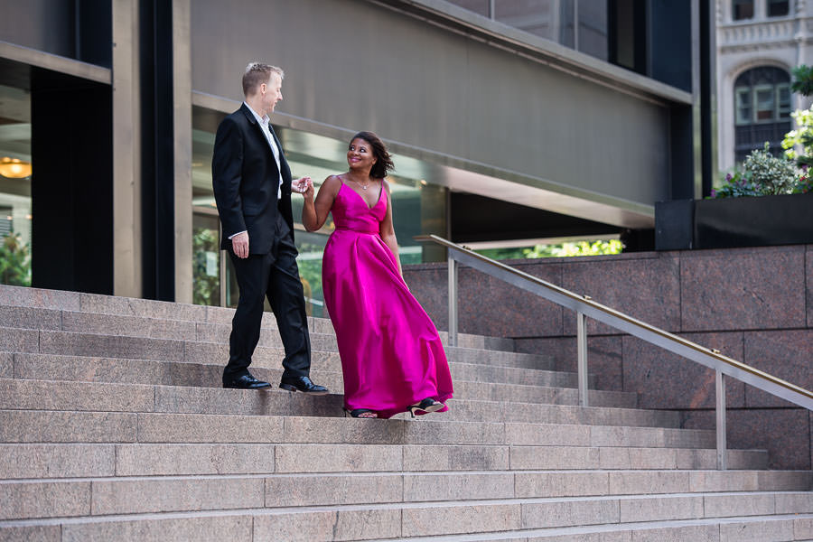 engaged couple in formal evening wear walk down stairs for their engagement session in downtown manhattan