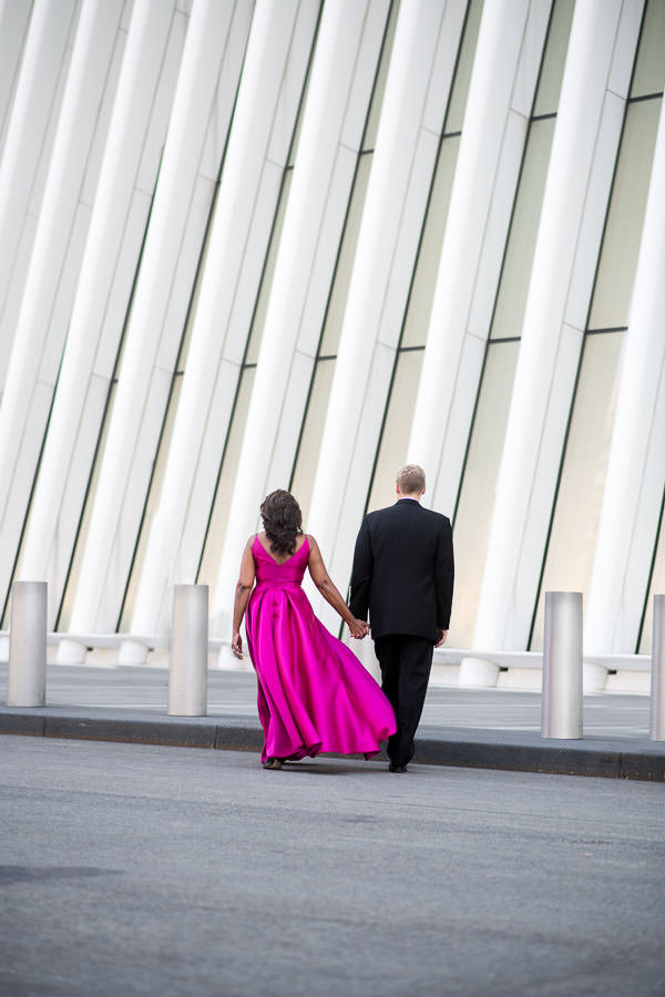 engaged couple walking by the oculus for their engagement session in formal attire