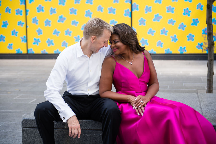 engaged couple sitting on bench with yellow background