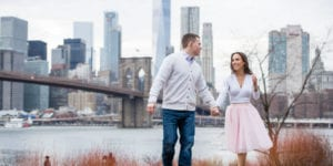 guy in white sweater and girl in pink tutu engagement session at brooklyn bridge park in dumbo nyc