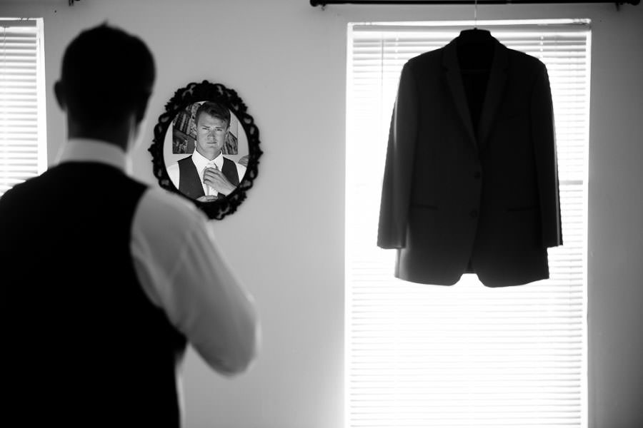 groom getting ready fixing his bow tie