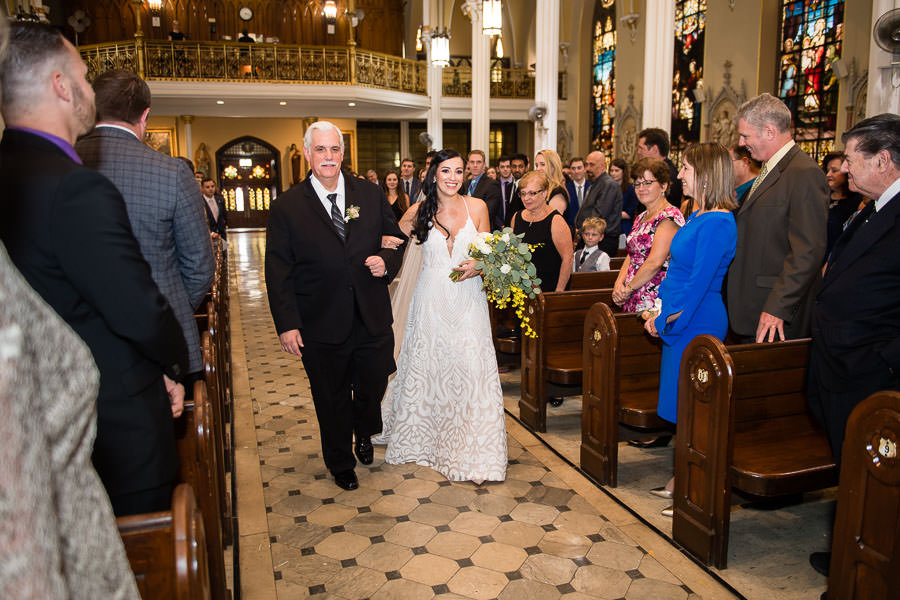 bride walking down the aisle at st anthonys church with her father