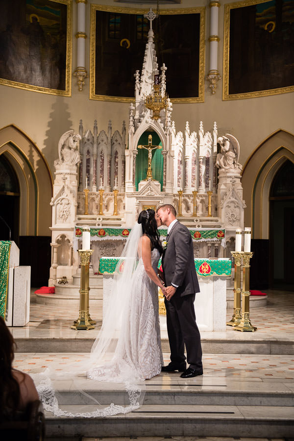 kiss at the altar at st anthonys church wedding in greenpoint