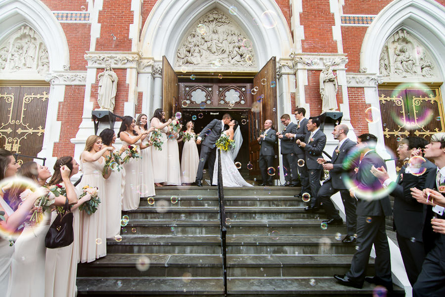 bride and groom kiss outside of anthonys church after wedding ceremony in brooklyn with bubbles being blown by guests