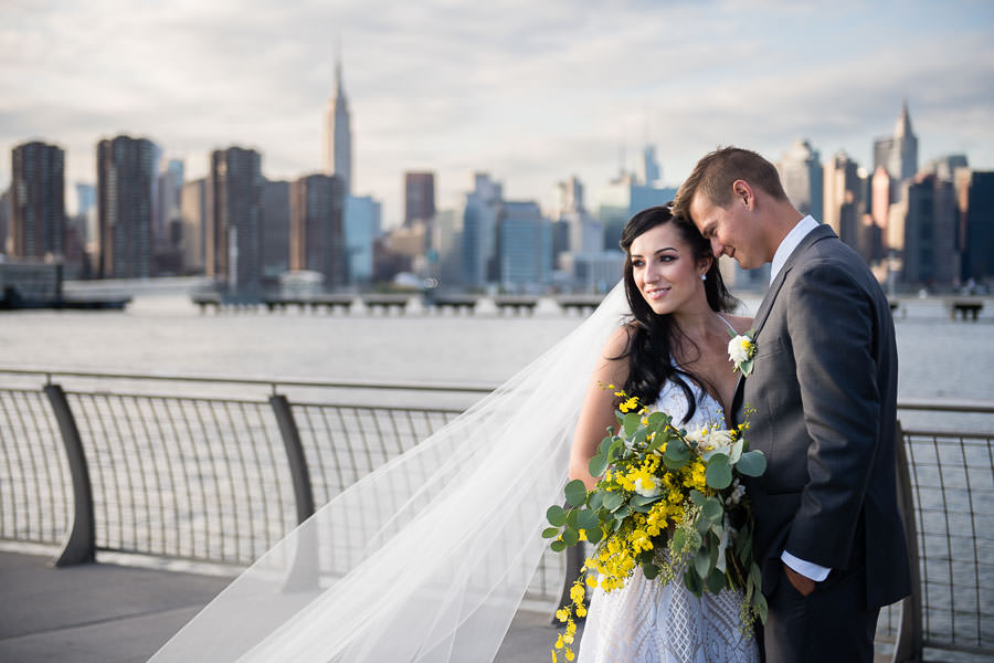 bride and groom hold hands by greenpoint loft wedding with nyc skyline in the background