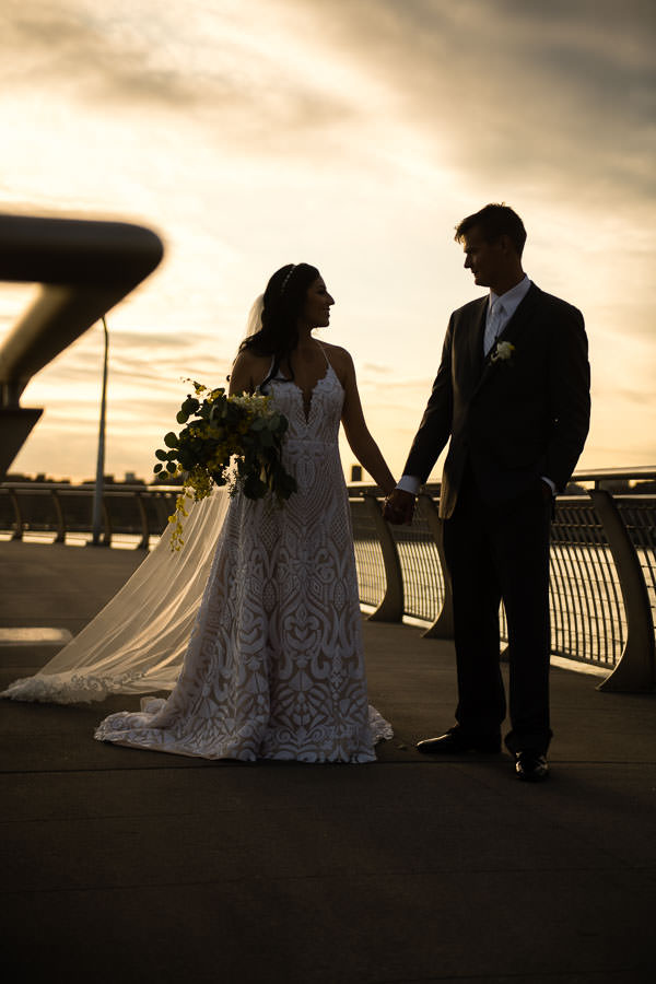 bride and groom with empire state building in the background at their brooklyn wedding at sunset by the water
