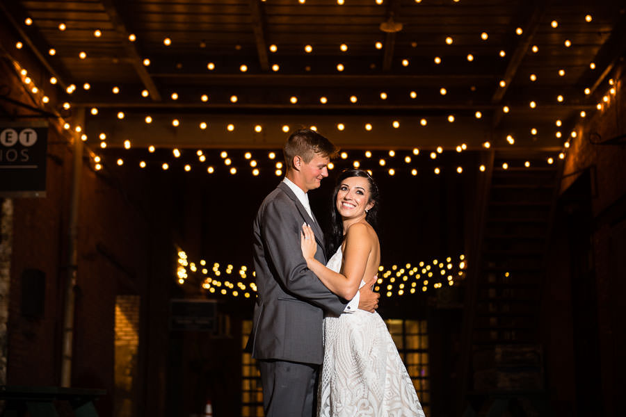 bride and groom in the alley at their greenpoint loft wedding in brooklyn with string lights