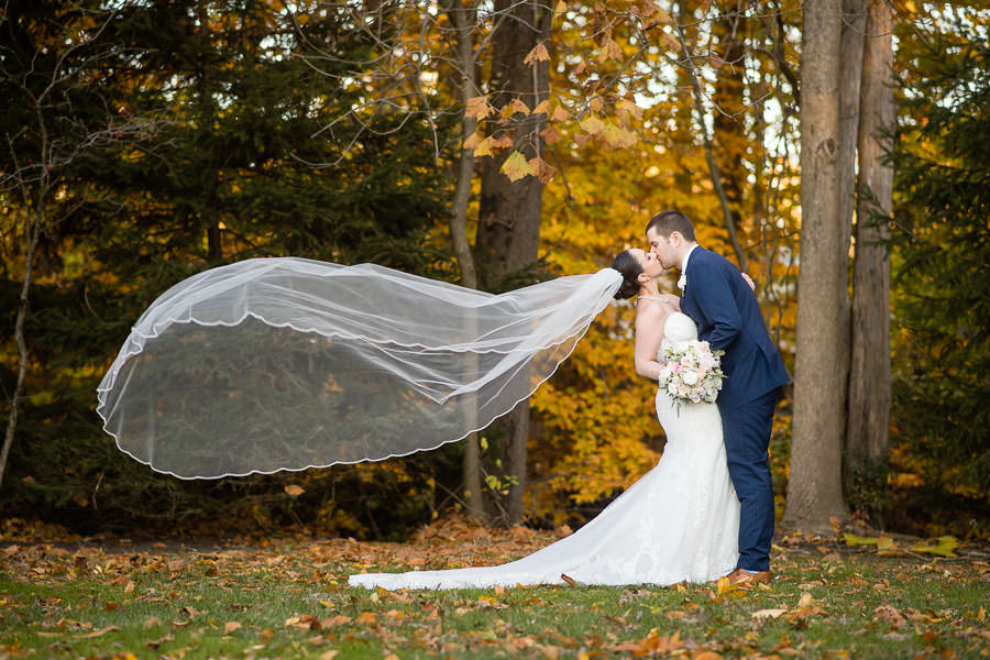bride's veil is flying in the wind with autumn leaves in the background as she kisses her groom during olde mill inn wedding
