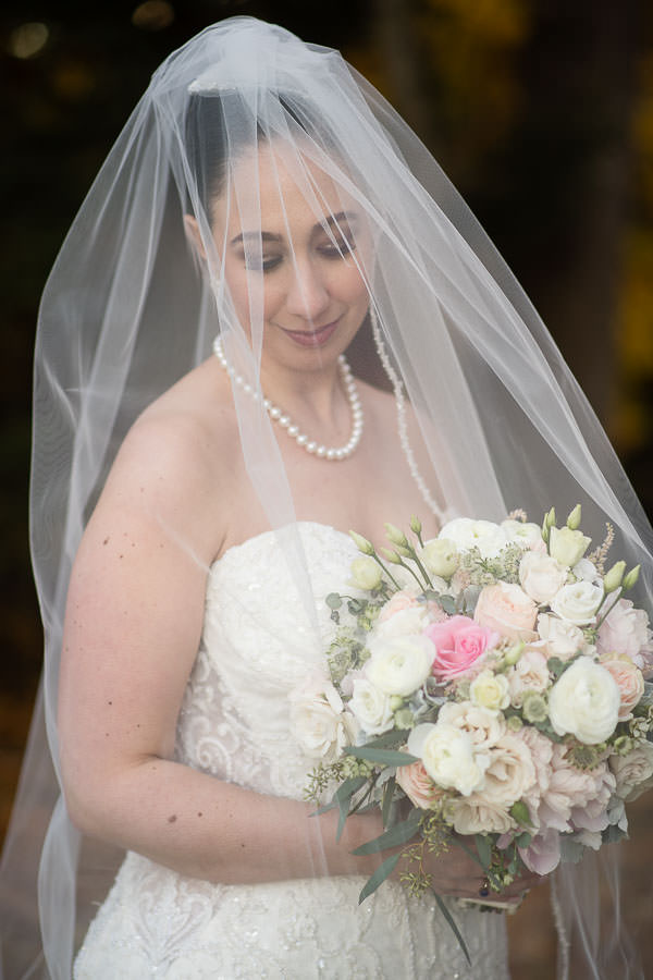 bridal portrait with veil and bouquet of flowers