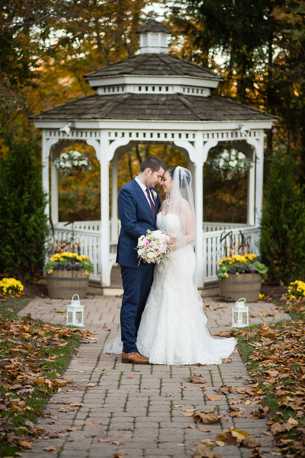 wedding couple in front of gazebo during autumn at olde mill inn new jersey
