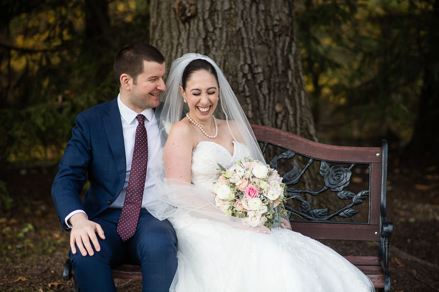 wedding couple sits on bench at olde mill inn new jersey