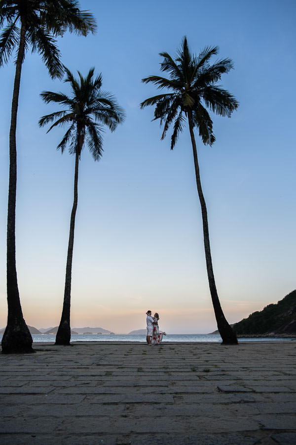engaged couple holding each other on beach with palm trees during sunset in rio de janeiro, brazil