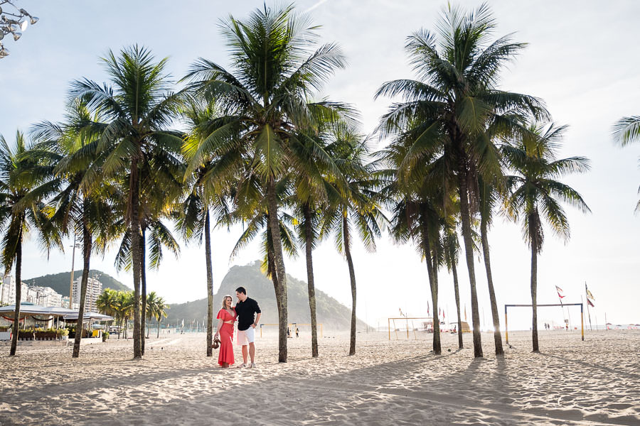 engaged couple on copocabana beach in rio de janeiro beach with palm tree and mountain in the background