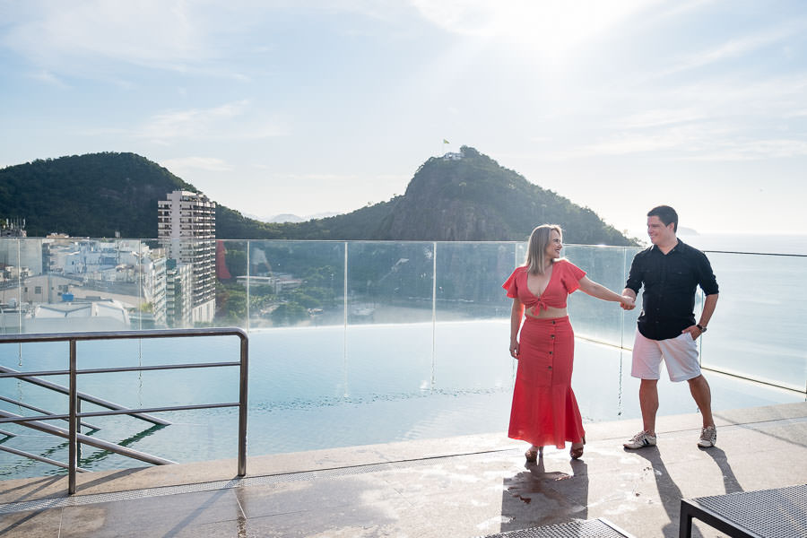couple holding hands by pool on windsor leme hotel rooftop in rio de janeiro brazil