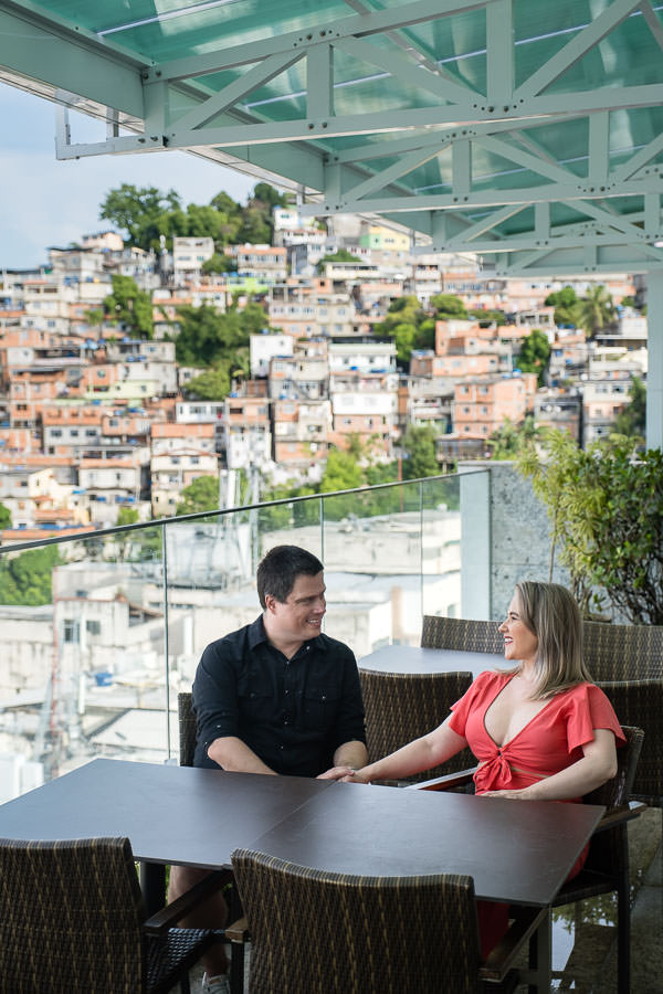 couple sitting with favelas in the background