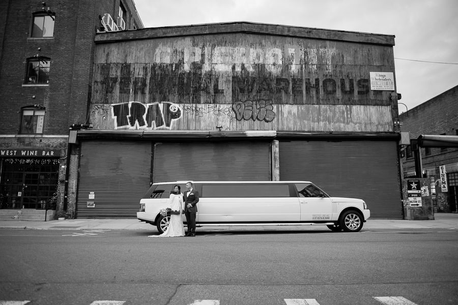 wedding couple in front of greenpoint loft standing by white limo