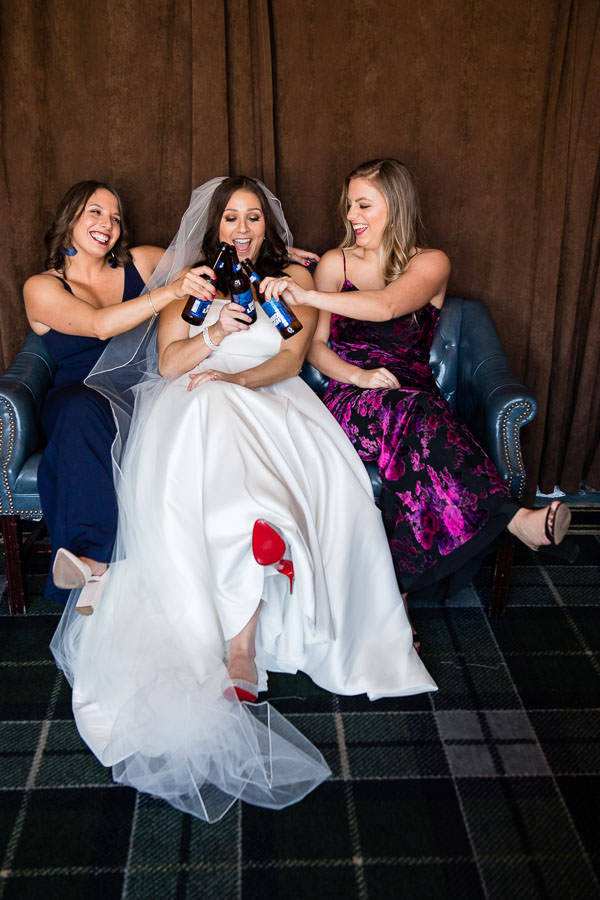 bride and bridesmaids drink bud light while wearing louboutins