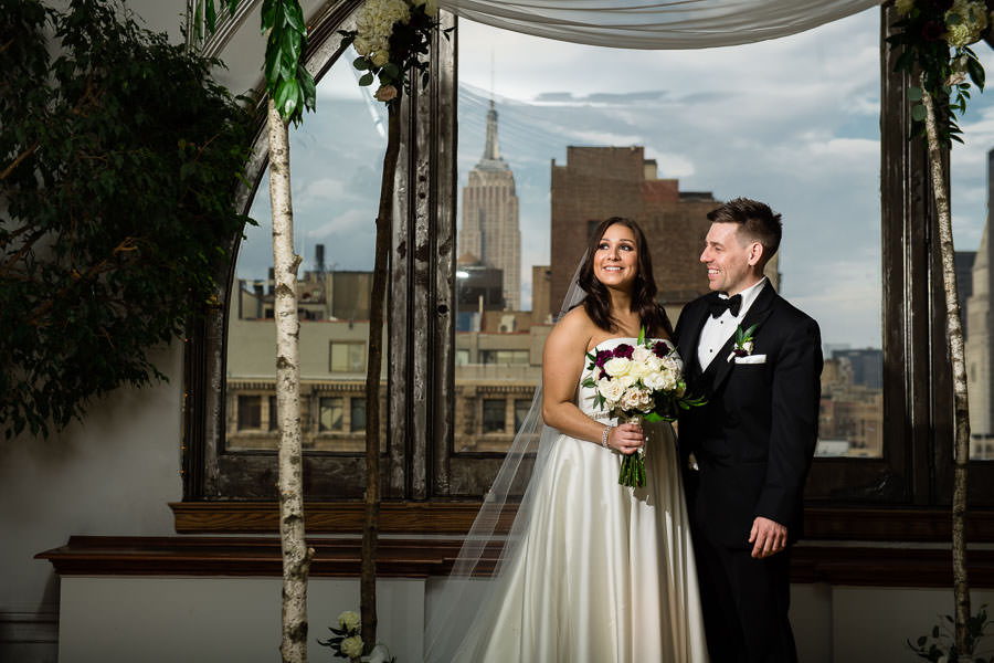 manhattan penthouse wedding with empire state building visible in the arch window