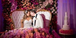 bride and groom pose by their sweetheart table designed by Gary Abramov Event Productions DBA Floral Art at the metropolitan ballroom