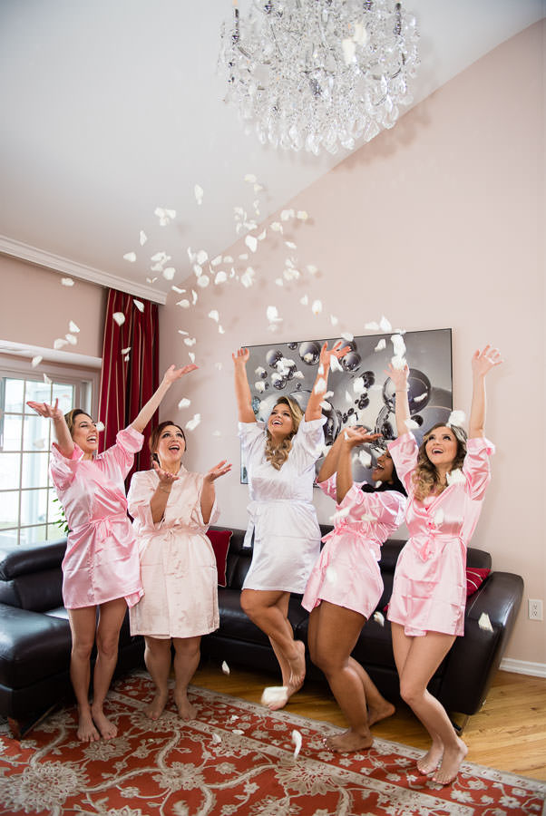 bride and bridesmaids throw flower petals in the air while they get ready