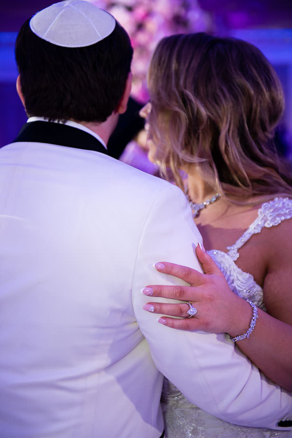 bride and groom dance during their wedding night with a close up of her engagement ring