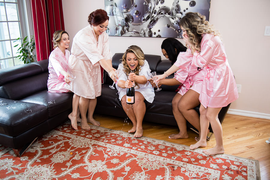 bride and bridesmaids open champagne during wedding day getting ready and it spills everywhere while they laugh