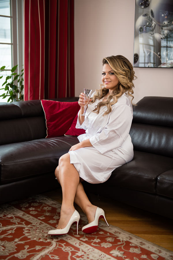 bride in her white robe and louboutins sipping champagne during bride prep on her wedding day