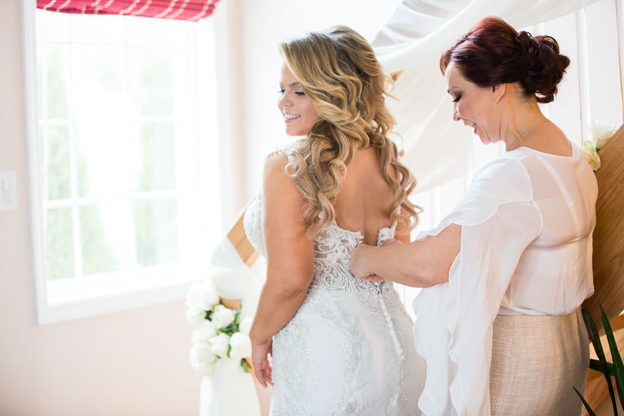 brides mom helping her put the dress on