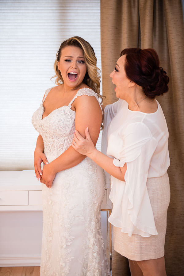bride and her mom getting ready before the wedding day starts