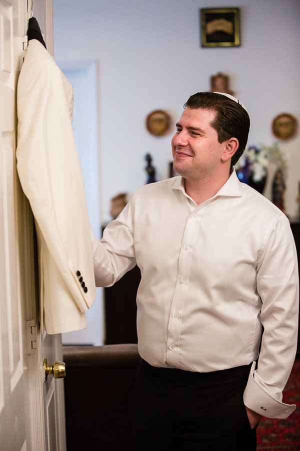 groom getting his white tuxedo before the wedding