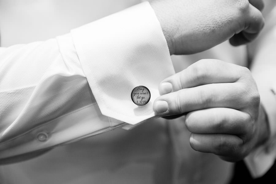 groom adjusting his cuff links before the wedding