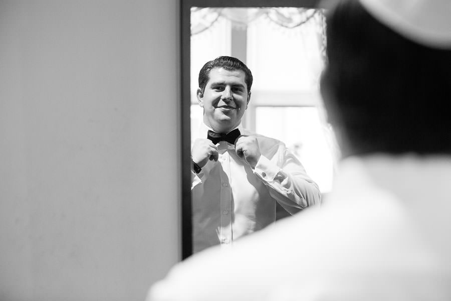 groom adjusting his bow tie before the wedding