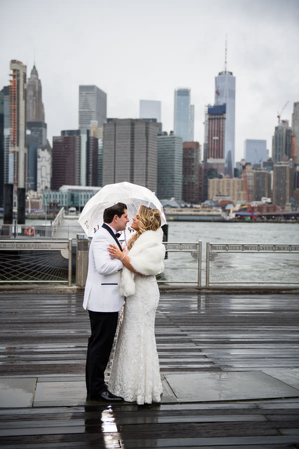 bride and groom photo session in brooklyn bridge park with nyc skyline on a rainy day