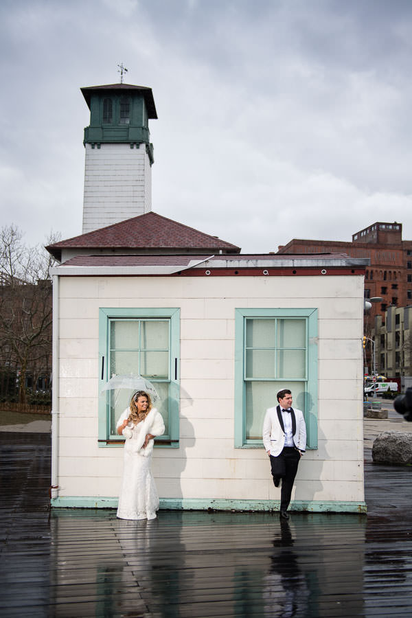 bride and groom pose next to brooklyn ice cream factory