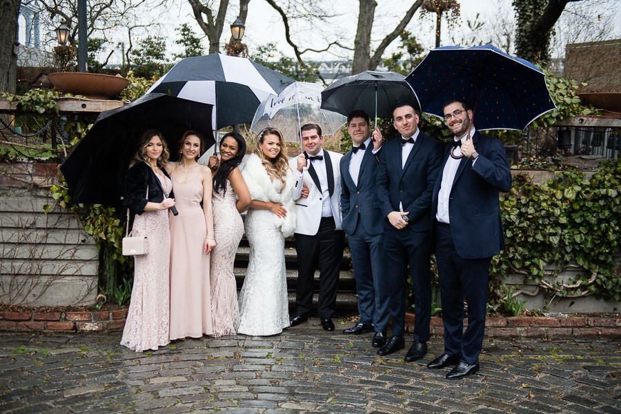 bride and groom with bridal party in the rain at their wedding photo session in brooklyn bridge park