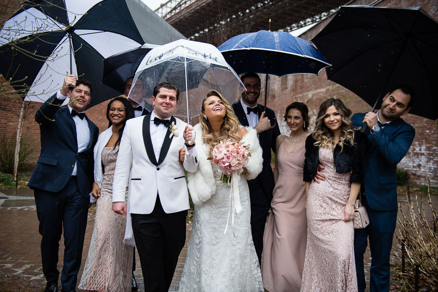 bride and groom walk with bridal party in the rain at their wedding photo session in brooklyn bridge park