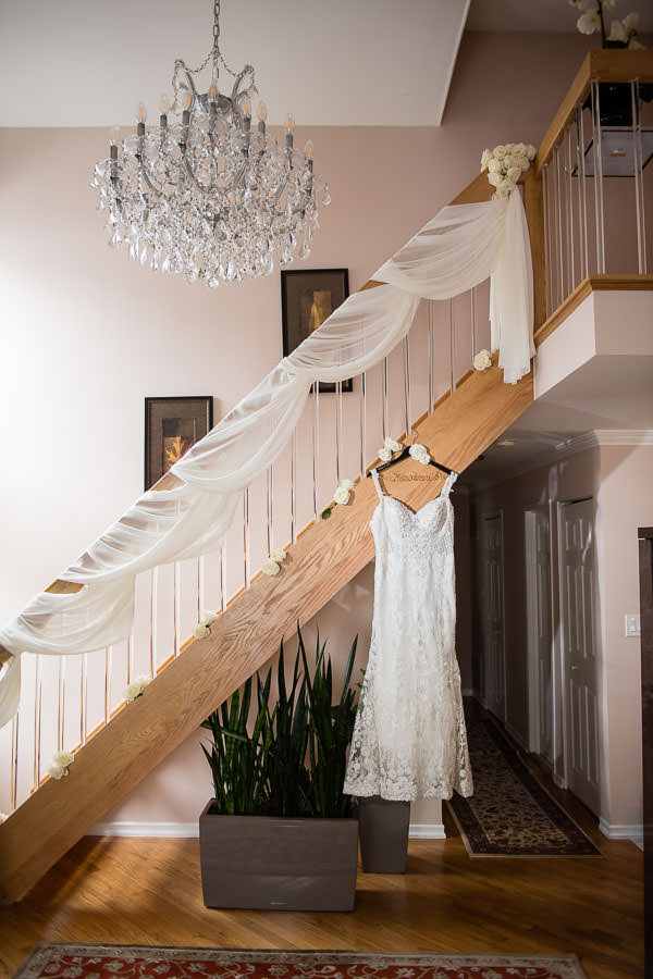 brides wedding gown hanging from stairs