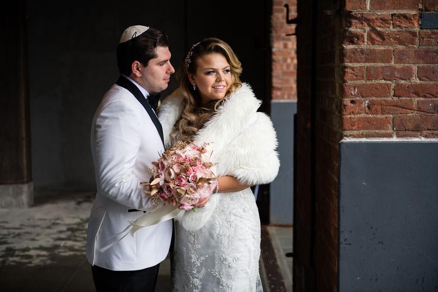 bride and groom pose at brooklyn bridge park in dumbo wedding