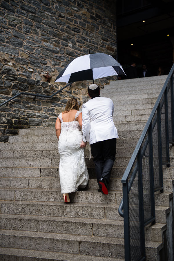 bride and groom walk up the stairs in their louboutin shoes under an umbrella